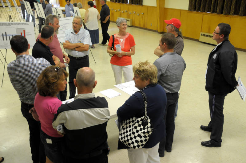 South Dundas councillors and staff, spokesmen from EDP Renewables and local residents chat about the proposed South Branch Wind Farm II project during an open house Aug. 5, 2015 at Matilda Hall in Dixons Corners. (Brockville Newswatch/Bill Kingston)