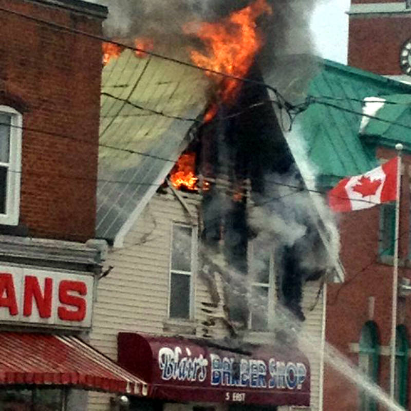 In this Monday, Feb. 29, 2016 photo provided by Rodney Linderman, flames shoot from an upstairs floor of a Main Street building in Athens, Ont. (Rodney Linderman via Newswatch Group)
