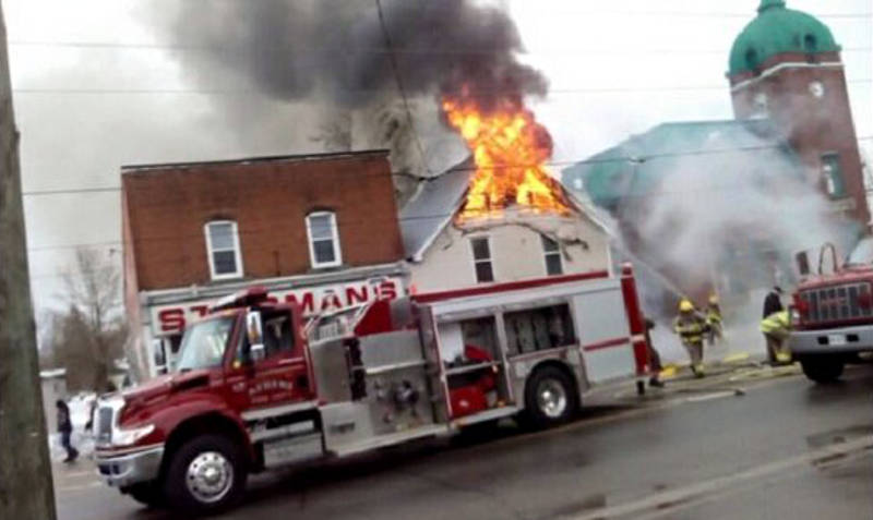 In this Monday, Feb. 29, 2016 photo provided by Rodney Linderman, Athens Township firefighters tackle the flames from the second storey of a barber shop on Main Street in Athens, Ont. (Rodney Linderman via Newswatch Group)