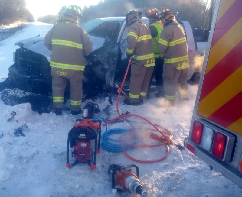 In this Thursday Feb. 18, 2016 photo provided by the North Grenville Fire Service, firefighters work to free a driver from his pickup truck after a collision with a railway plow on Dennison Road near Kemptville, Ont. (North Grenville Fire Service via Newswatch Group)
