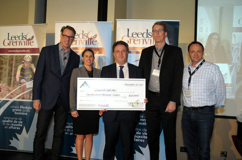 Members of Launch Lab at The Innovation Center receive a cheque for $27,000 from MP Gord Brown, center, on Friday, Nov. 18, 2016 during an economic development summit in Kemptville, Ont. The money will be used for the business acceleration program. (Newswatch Group/Bill Kingston)
